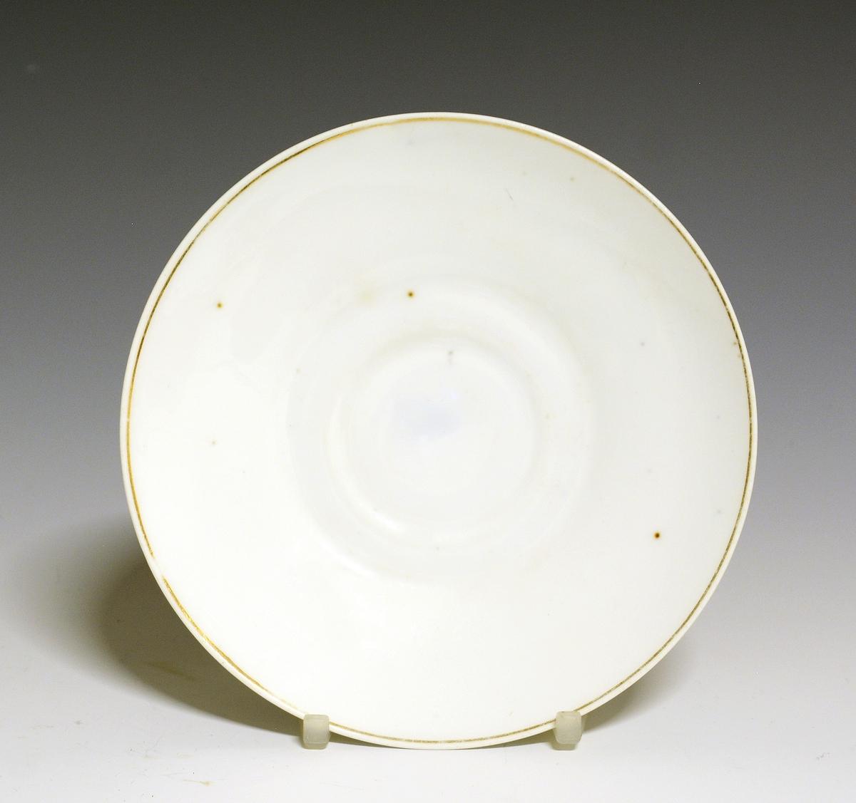 Skål til kaffekopp (el. tekopp) i porselen med hvit glasur. Gullstripe langs kantranden. Modell: 96 Fabrikkmerke: Blått anker med PP Finnes i priskuranten for 1888, tavle 3.
