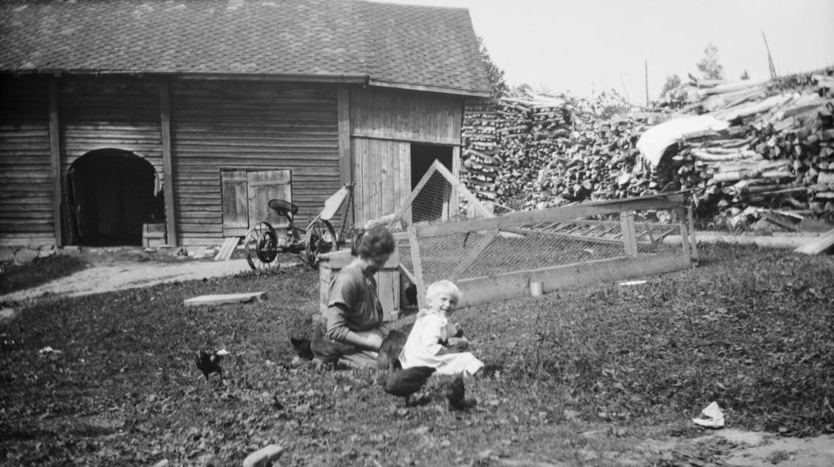 Kvinne og barn på tunet, antakelig på Linjordet i Østre Gausdal
