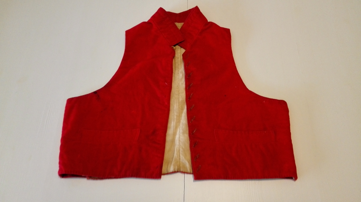 1 vest.  Röd klædes vest med oputstaaende krave. Har hat 11 sölvknapper, der nu er borte.  Ryggen rödfavet dreid(?). To indvendige paasydde lommer av grovt lintöi, foret med linlærred. Vesten er i 1859 kommet til Ortnevik fra Vinje i Vossestranden.  Gave fra Randine Fitje, Ortnevik.