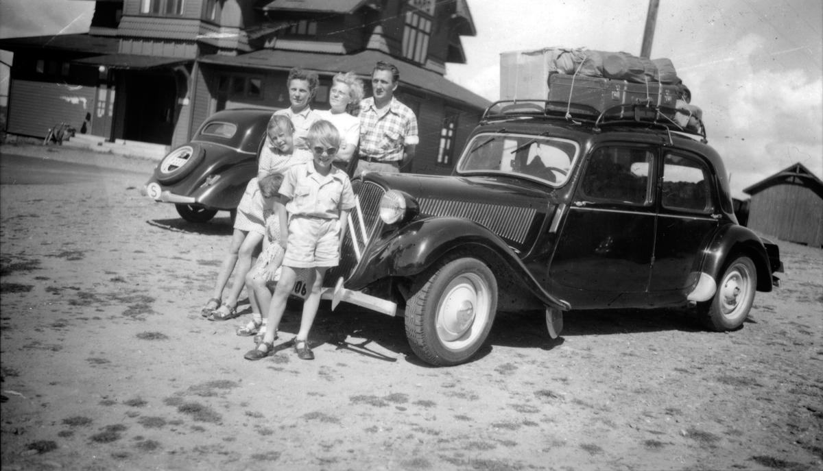 En familj på semester vid bilen med packning på taket.