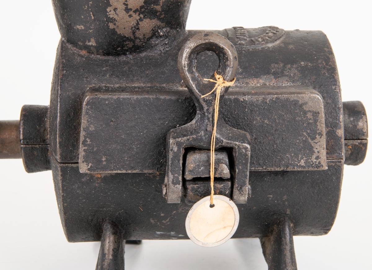 Köttkvarn av gjutjärn, cylindrisk på fyra fötter. Handvev. Verkar genom en rad fasta, korta knivar och korta trubbiga pinnar på valsen.Tratt överst. Märkt: Engda & Nielsen Kristiania.