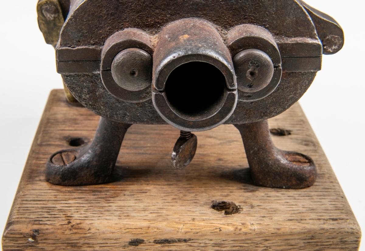 Köttkvarn av gjutjärn med fyra ben, fäst på träplatta. Tratt överst. Handvev. Två valsar med snedställda kantiga järn. Märkt; Ankarsrum.
