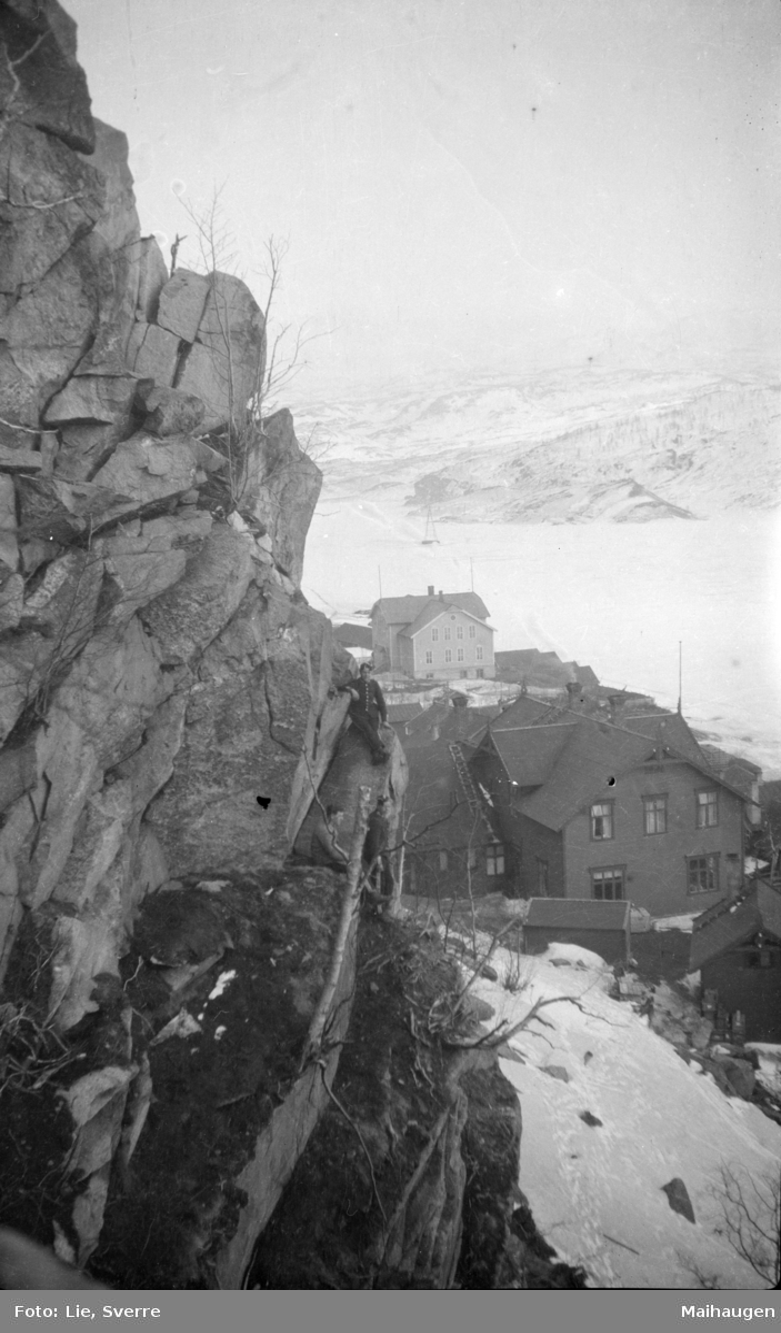Miljø med tett husklynge under en fjellknaus. Med tre soldater. Islagt vann eller fjord i bakgrunnen.