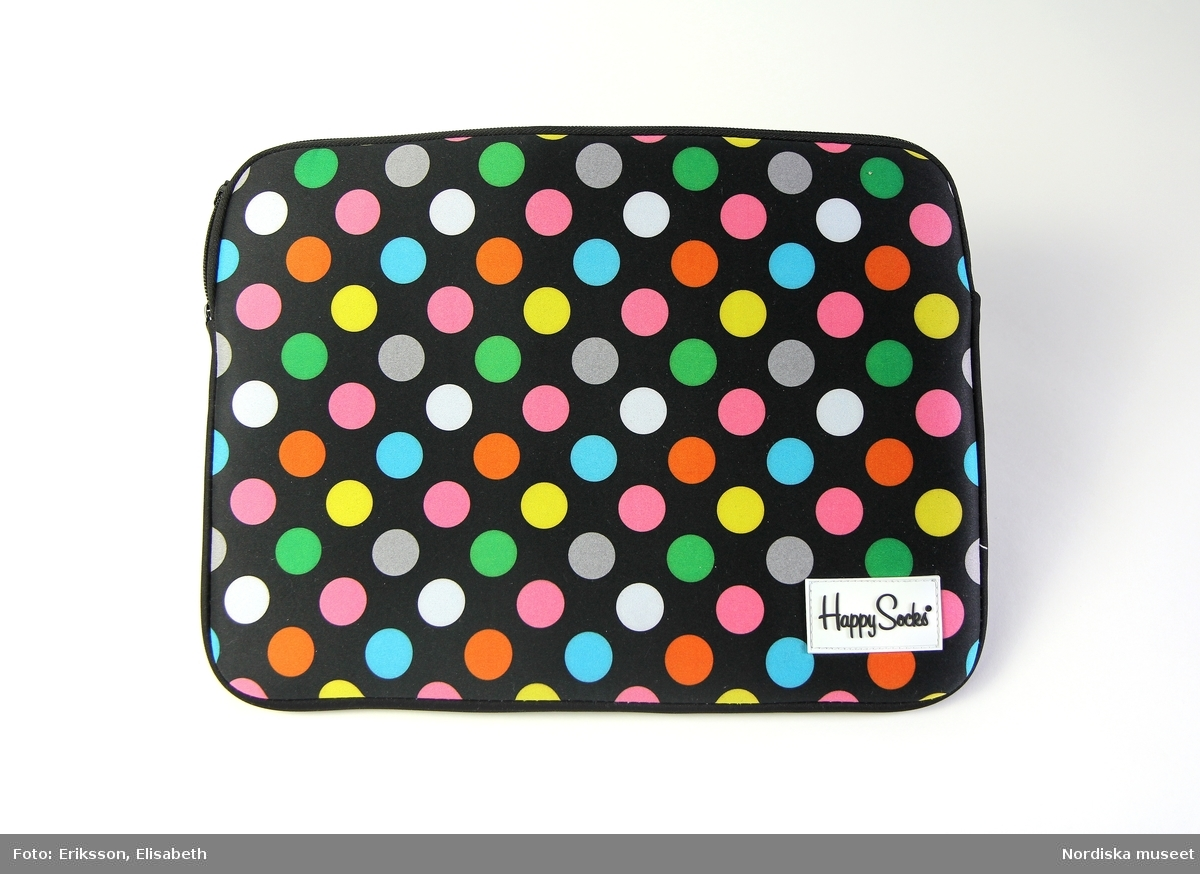 """Ett laptopfodral i syntetiskt tyg. Formen är rektangulär.  Alla sidor är av tjockt vadderat tyg. En dragkedja löper längs ena långsidan. Tyget är mönstrat med stora prickar (ca 2 cm) i rosa, ljusgrå, vit, ljusblå, orange, grön och gul mot en svart bakgrund.  Längst ner i högra hörnet på framsidan är en fastsydd vit lapp av gummi (5,5 cm bred) med texten """"Happy Socks®"""" i svart. Inuti fodralet sitter en liten vit lapp fastsydd i ena kortsidan med texten """"Happy Socks® Designed in Sweden"""" på ena sidan, och på andra sidan står det """"DRY CLEEN ONLY"""" högst upp, samt tvättsymboler och materialinformation på engelska, tyska, spanska, franska, italienska, japanska och nederländska. I nederkant av lappen står det """"Made in China"""" och """"www.happysocks.com"""".  /Elise Wargentin 2015"""