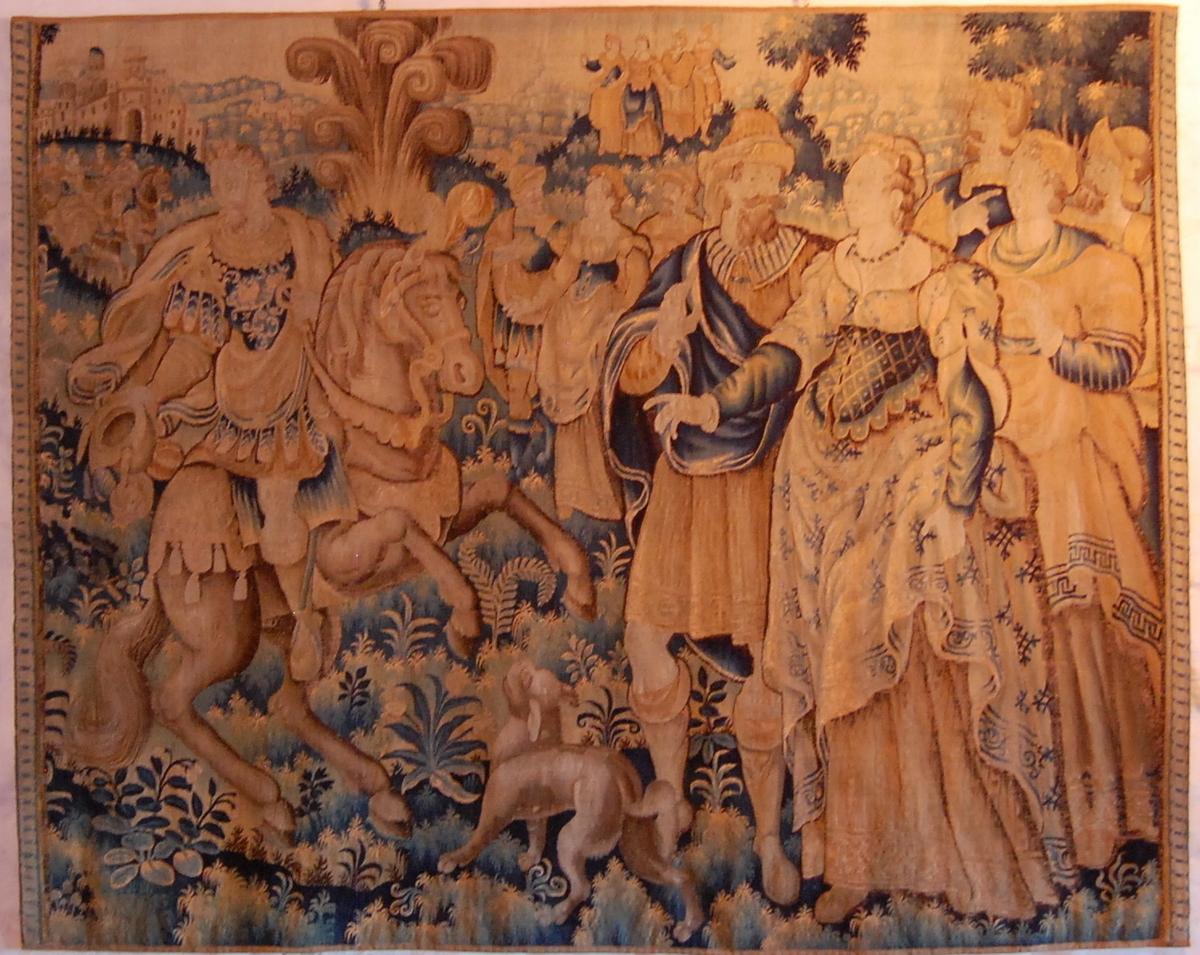 Viser utescene med figurer. Rytter til hest til høyre i motivet, stående figurer i grupper til venstre. I bakgrunnen skimtes en borg og grupper med mennesker.