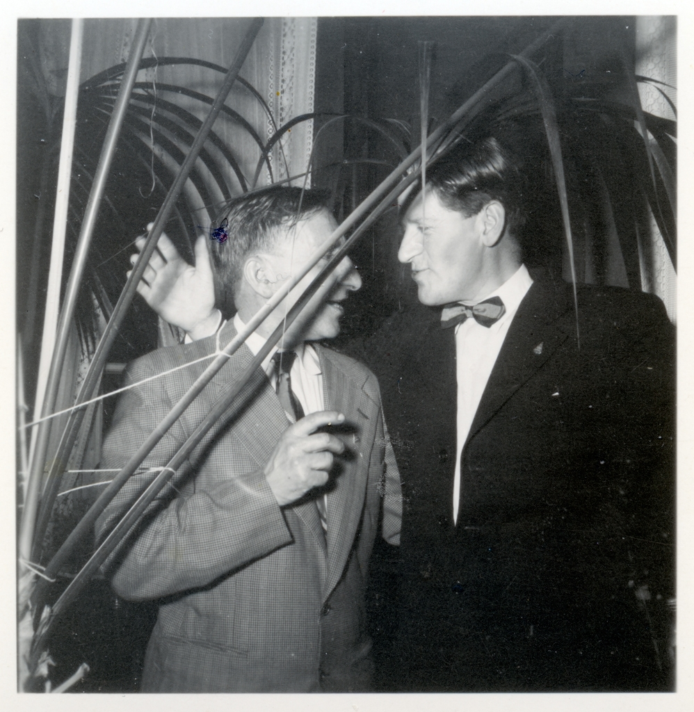 Två män står och pratar vid en fest anordnad av Monarks cykelverkstad för personalen. Ena mannen skyms av en större krukväxt.  Lennart Eriksson, Idrottsmagasinet, till höger