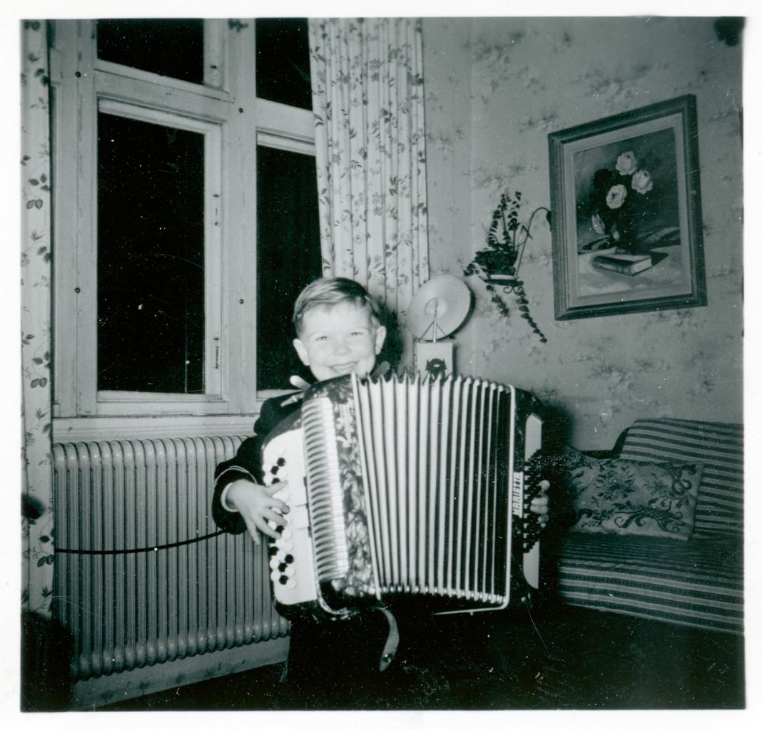 En pojke spelar på ett dragspel. Han ler mot kameran.