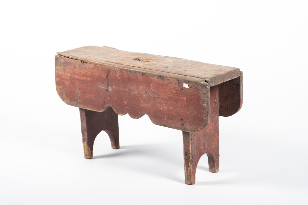 Rektangulær krakk. I sitteflaten er det skåret ut et rektangulært håndtak. Krakken har utskårne sarg på langsidene som forbinder bena tilhverandre.