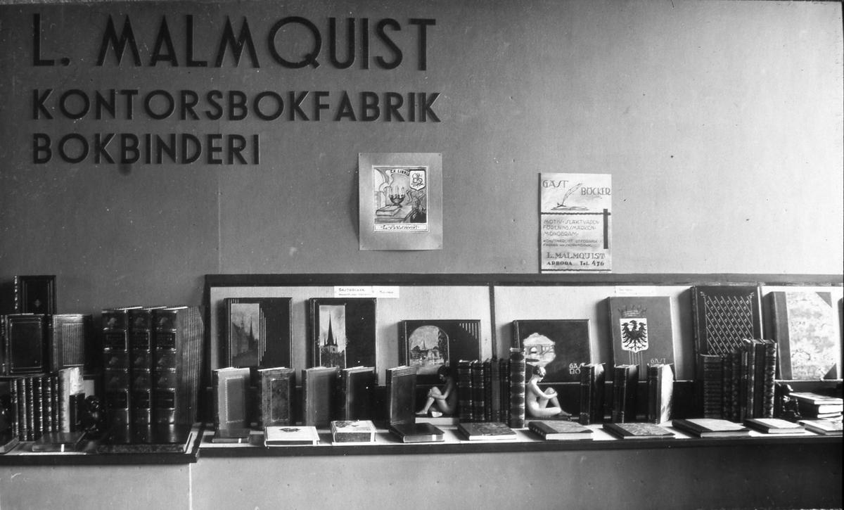 Arbogautställningen. Denna monter tillhör Malmkvists bokbinderi som ligger på söder i Arboga. Skinnband med marmorerade pärmar. Bokstöd i form av nakna unga kvinnor.