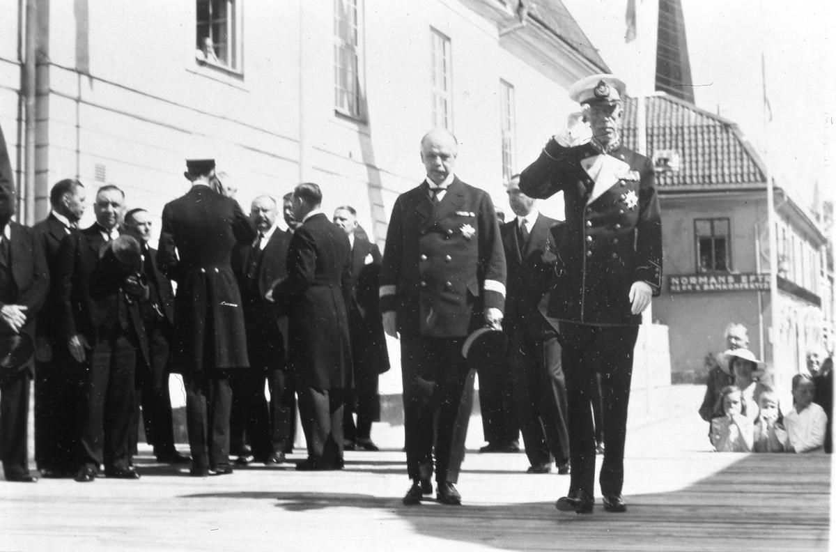 Kung Gustaf V och landshövdingen Valter Murray tackar för mottagandet. De är i Arboga för att delta i Riksdagens 500-årsjubileum. De står på en uppbyggd scen framför Rådhuset. Publik står nedanför podiet. I bakgrunden ses butiken Normans Efterträdare, Damkonfektion. (Arbogautställningen pågår samtidigt).