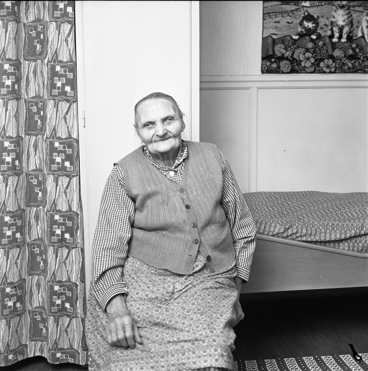 Kvinna, 90 år, iklädd väst och kjol. Hon sitter intill sin säng. På väggen, över sängen, hänger en bonad med katter. Till vänster, om kvinnan, hänger ett draperi.