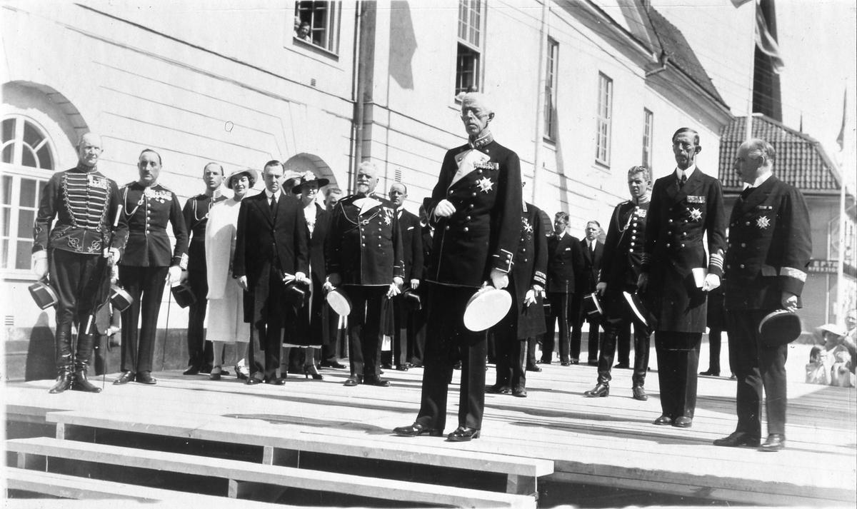 I Arboga firas Riksdagens 500-årsjubileum. Kung Gustaf V, och delar av den kungliga familjen, närvarar. Här är en uppbyggd scen, framför Rådhuset. Konungen mottager Kungssången, som spelas av Livgrenadjärregementet (I3) från Örebro. De står uppställda på Stora torget (utanför bild). Bakom kungen står prins Wilhelm och intill honom landshövding Valter Murray. Till vänster, efter de båda uniformerade männen, står borgmästare Wilhelm Wester (mörk överrock) tillsammans med sin hustru (vit hatt). (Arbogautställningen pågår samtidigt. Kungen ska hinna med ett kort besök där också).