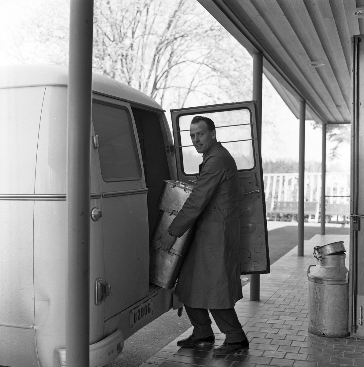 Bertil Häll lastar mat från AB Stig Dahlberg Storkök i Medåker. Stora kantiner ska in i skåpbilen. En stor mjölkkanna står bredvid.