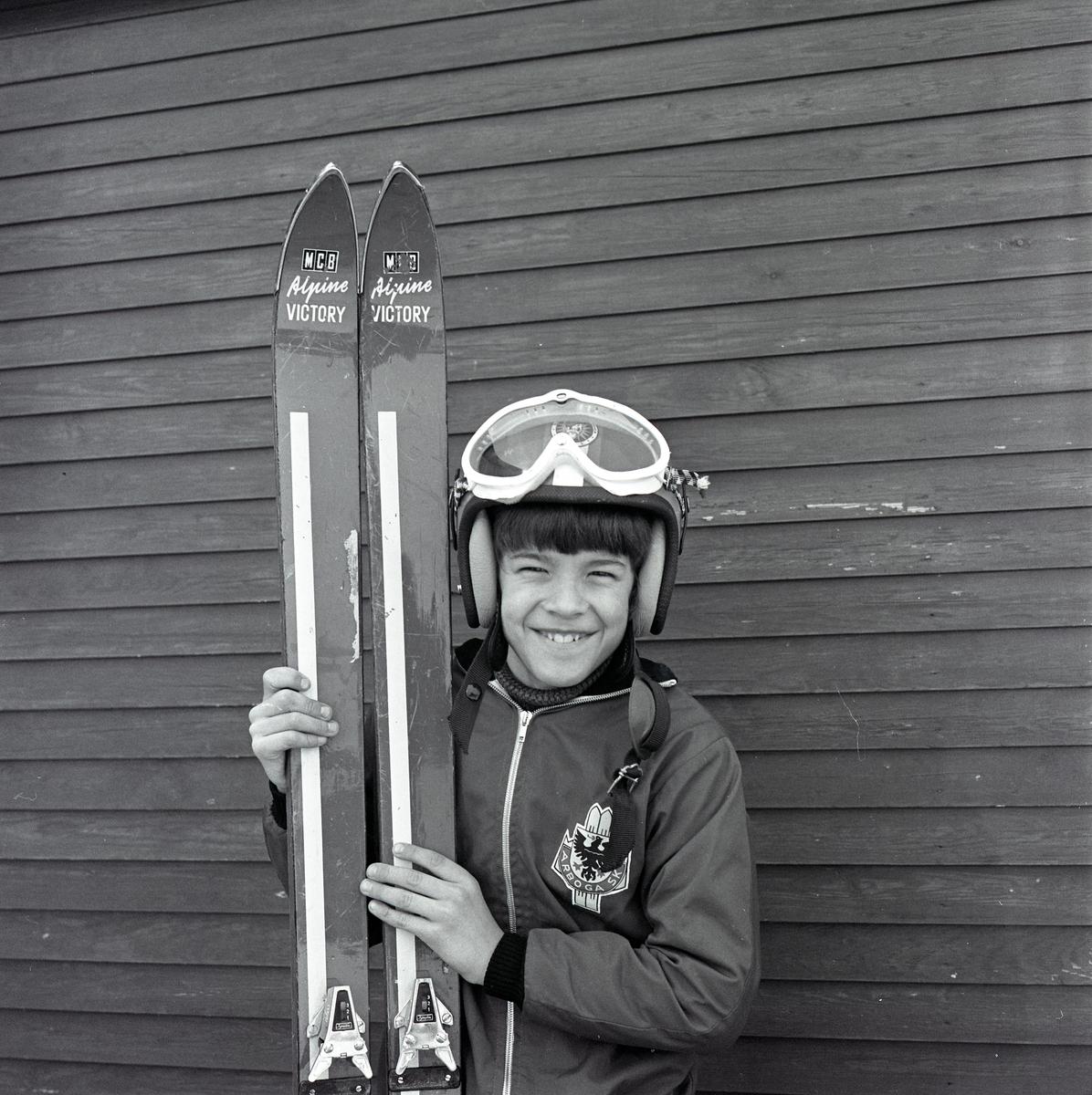 En glad Anders Winter, iklädd hjälm och glasögon. Han håller i ett par skidor. Pojke med skidor.