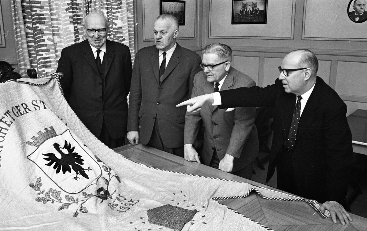 """Fyra kostymklädda män tittar på en fana med texten """"Enighet ger styrka"""". Från vänster: Gustav Johansson (kallad Murar-Gustav), Holger Eklöf, Axel Fritiof Strandberg (kallad Atchy) och okänd. De befinner sig i Arbetareföreningens lokal. Interiör."""