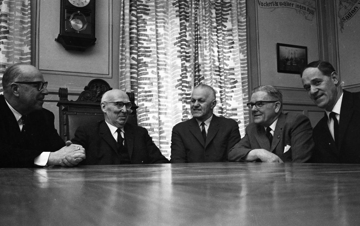 Fem herrar vid bordet. Från vänster: okänd, Gustav Johansson (Murar-Gustav), Holger Eklöf, Axel Fritiof Strandberg (Atchy) och Sigurd Granberg. De befinner sig i Arbetareföreningens lokal med väggdekorationer i bakgrunden. Gustav sitter på ordförandestolen.