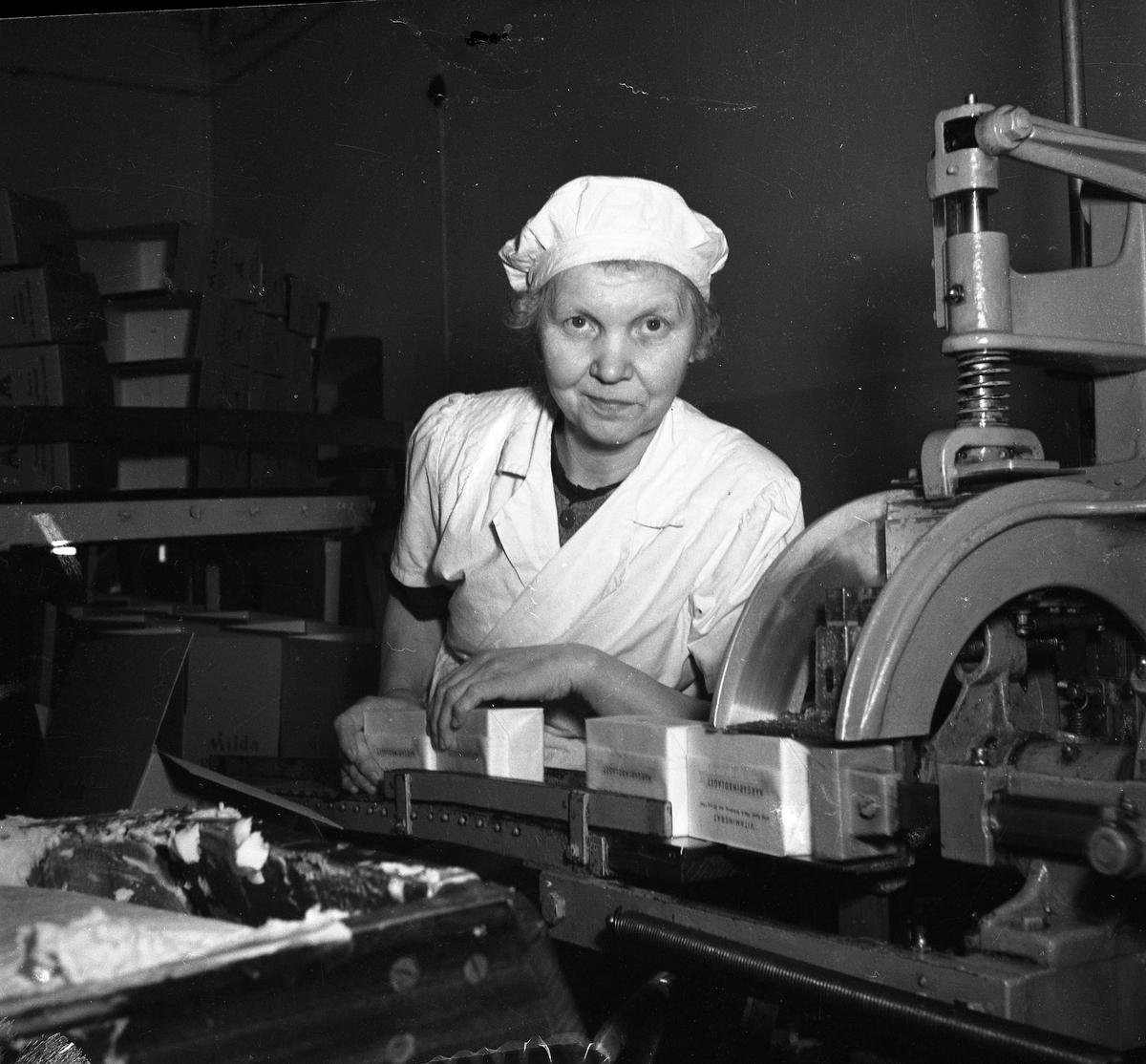 Arboga Margarinfabrik, interiör. Kvinna som skär margarin.  Edit Persson började sin anställning 1911, när hon var 14 år. Arbetet var tungt och mycket gjordes för hand. Arbetstiden varade från kl 06.00 - 18.00. Edit arbetade i fabriken tills den lades ner 1960. Det blev 49 år på samma arbetsplats.  Läs om Arboga Margarinfabrik i Arboga Minnes årsbok 1978 och Reinhold Carlssons bok Arboga objektivt sett.