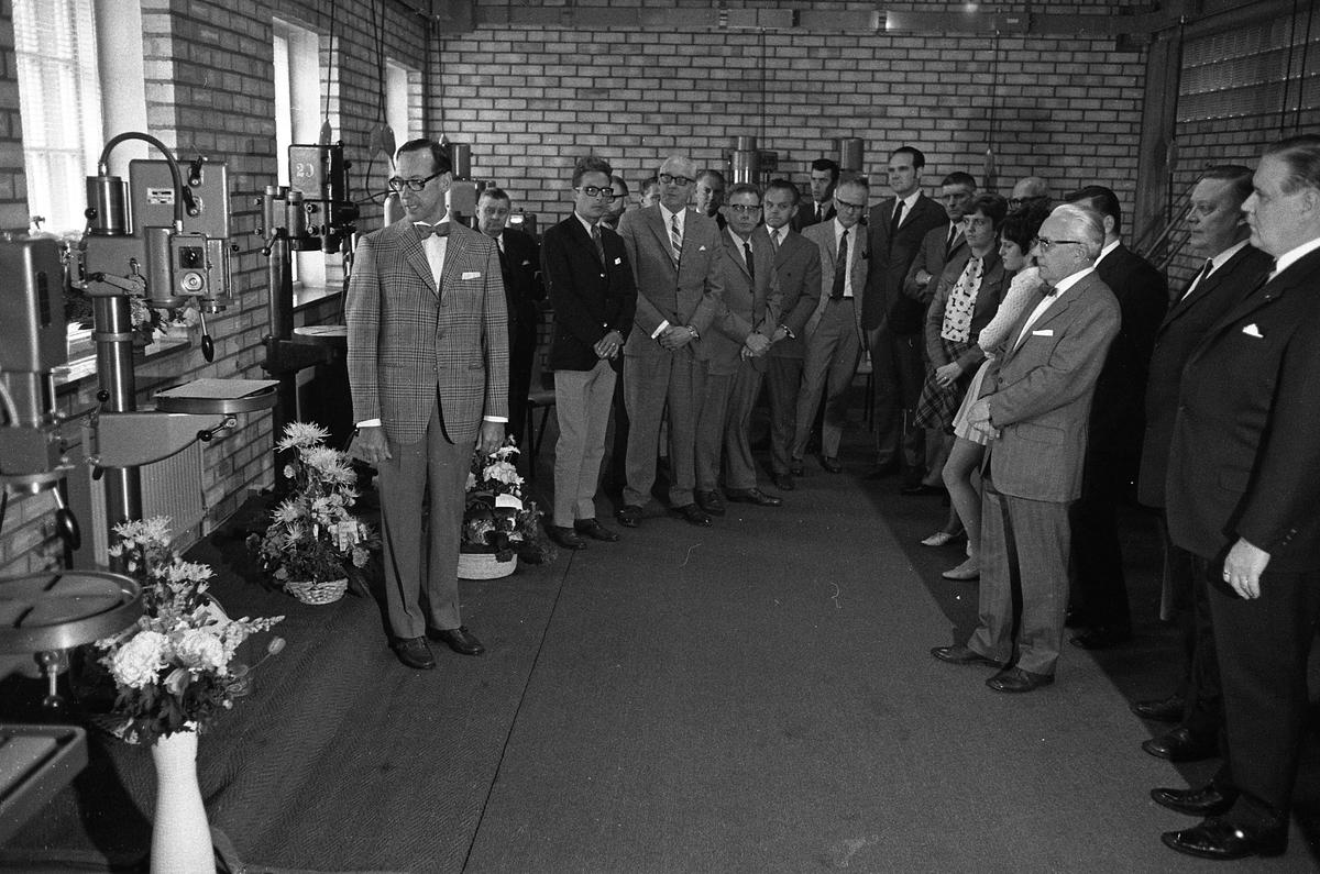Arboga Maskiner levererar jubileumsmaskin till kund, 1970-talet Många kostymklädda män och ett par kvinnor i blus och kjol är samlade vid några pelarborrmaskiner. Tre blomsteruppsättningar står mellan maskinerna. Hroar de la Cour håller anförande. Den långe, mörke mannen, vid kortväggen, är Göte Wahlfeldt  AB Arboga Maskiner startade 1934 och tillverkar borr- och slipmaskiner.