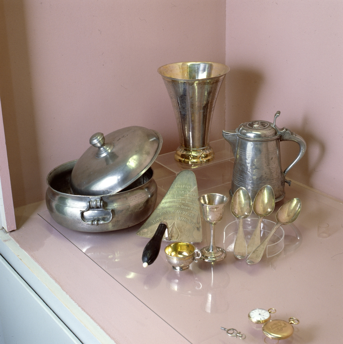 Arboga museum, samling. Föremål av silver och tenn. En pokal, en stånka, en skål med lock, en tårtspade, en punchbägare, en bägare på fot, tre matskedar och två fickur.