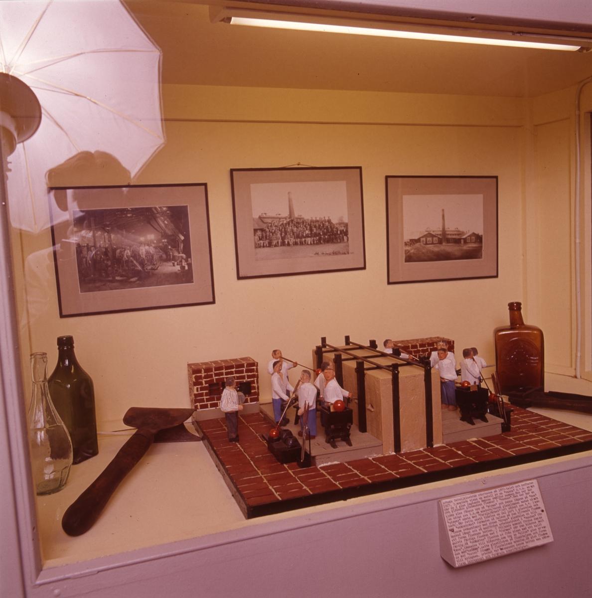 """Arboga museum, interiör. En modell föreställande glasblåsare, tre flaskor från Arboga Glasbruk, ett verktyg samt tre inramade fotografier från glasbruket. Fotograf Reinhold Carlsson, och hans paraplyblixt, speglar sig i monterglaset.  Uppgifterna om vilket år glasbruket etablerades varierar; 1867, 1870 och 1874 är exempel.  Bolagsordningen, för Arboga Glasbruks AB, stadfästes 1875. Bruket anlades nära hamnen och järnvägen. Buteljer fraktades till Stockholm med lastångaren """"Trögelin"""". På glasbruket tillverkades ca 400 olika sorters flaskor, olika storlekar inräknade. Glasbruket lades ner 1928.  Läs om Arboga Glasbruk i Hembygdsföreningen Arboga Minnes årsböcker 1982 och 2011."""