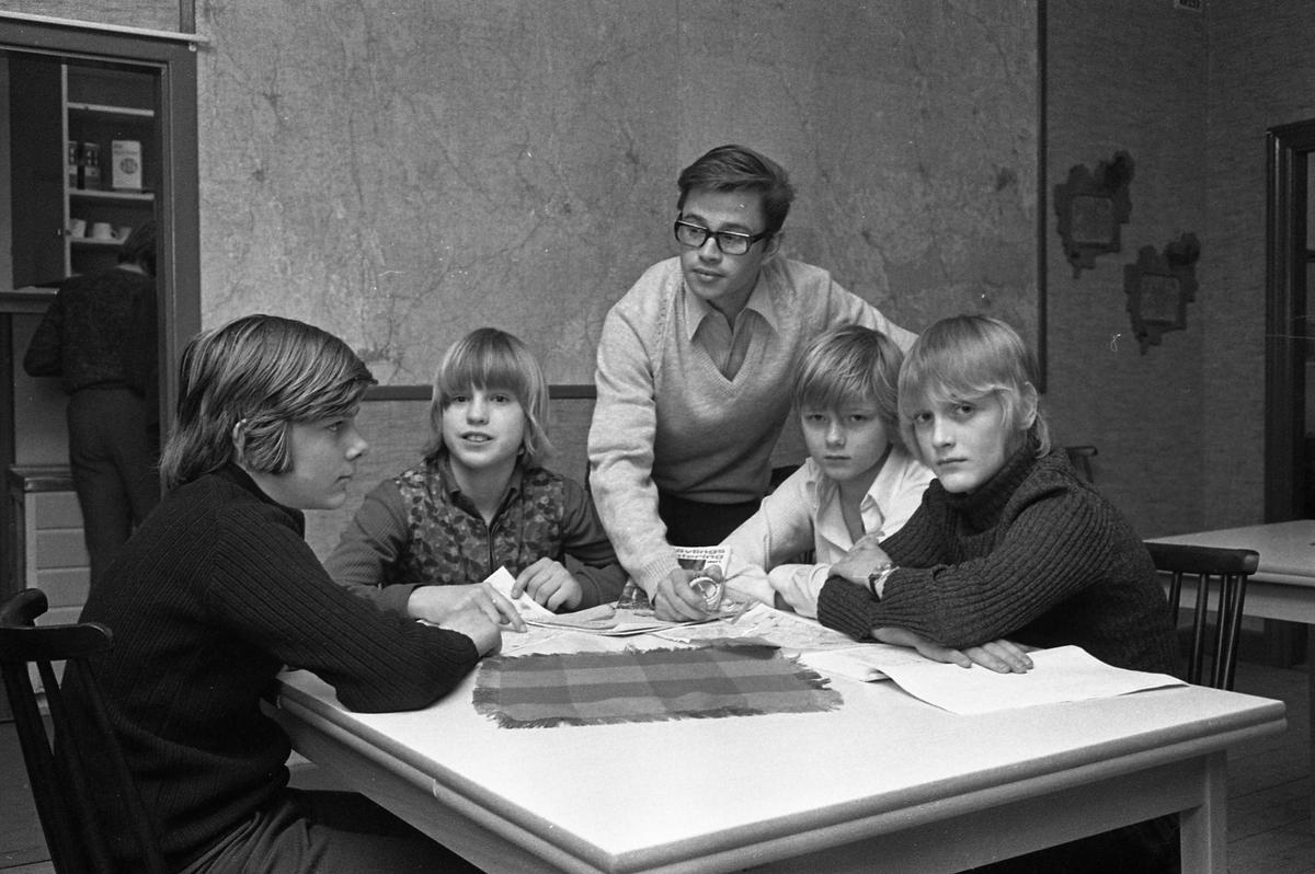 Arboga OrienteringsKlubb. Fyra pojkar sitter runt ett bord. En man lär dem hur kompassen fungerar. På väggen, bakom dem, hänger en stor karta. I rummet intill finns ett kök.