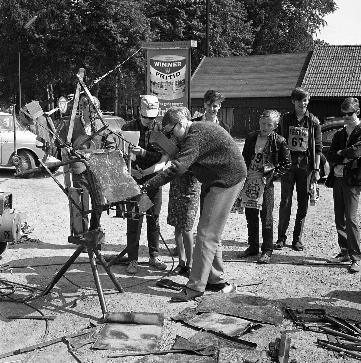 """Arboga Tekniska skola. Äldre elever har hittat på en besvärlig uppgift till nykomlingarna. """"Skändning"""" kallas det. En grupp ungdomar är samlade utomhus. Någon svetsar. Bilar i bakgrunden. Längst till höger står Per Bengtsson."""