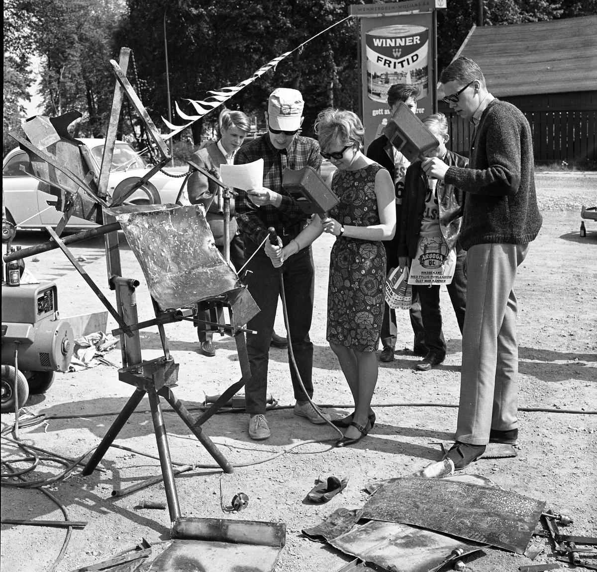 Arboga Tekniska skola. Äldre elever har hittat på besvärliga uppgifter till nykomlingarna. En kvinnlig elev svetsar medan andra ser på. I bakgrunden syns en bil.