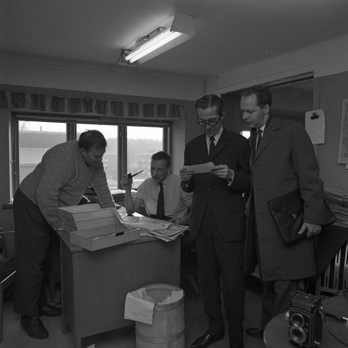 Arboga Tidning, personal och interiör. Fyra män ses i rummet. Två män er på ett papper som den ene håller i. Mannen med papperet är klädd i kostrym och slips. Den andra mannen, Willy Johansson, har överrock och en portfölj under armen. I bakgrunden diskuterar två män. Den ene står lutad över skrivbordet, den andre sitter ner och har en pipa i handen. Kontoret ligger på andra våningen. Tidningsbuntar syns i bakgrunden. En papperskorg står på golvet. På bordet, i förgrunden står en kamera.