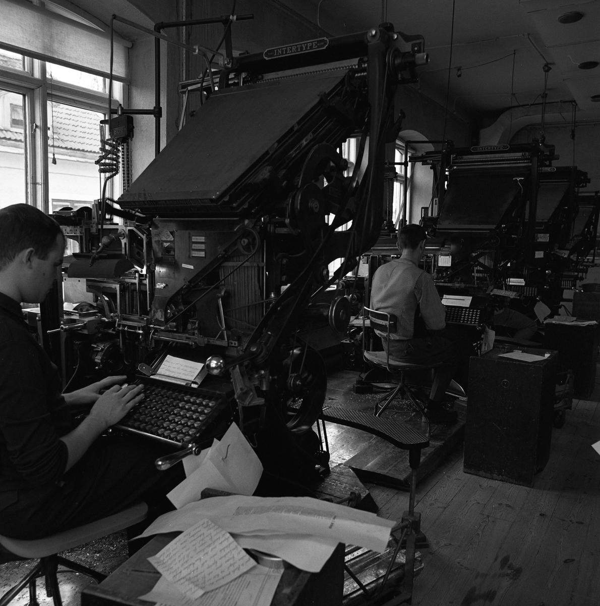 Arboga Tidning, personal och interiör. Två män sitter vid var sin sättningsmaskin. Maskinerna har tangentbord som männen skriver på. Handskrivna lappar ligger vid deras sida.