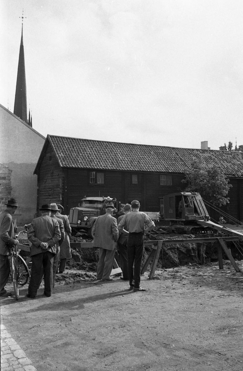 Några män är samlade vid en stor grop. En grävmaskin och en lastbil är i arbete. Två bockar är uppställda som fallskydd. Männen står med ryggarna mot fotografen. En av dem har en cykel. I bakgrunden ses tornet på Heliga Trefaldighetskyrkan.