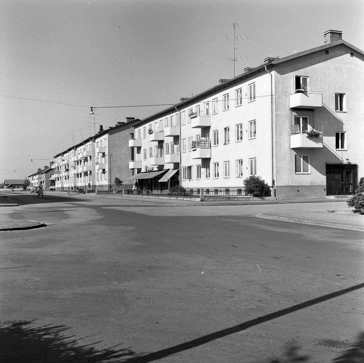 Flerfamiljshus i Vasastaden. Porten på gavlen har adress Stationsgatan 2. Längre bort på gatan syns en kvinna och en bil.