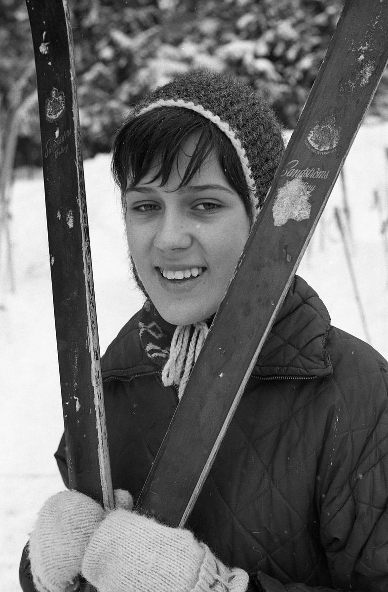 Gunvor Andersson deltar i skidtävlingen AT-loppet. Här står hon med sina längdskidor. Hon har mössa och lovikavantar på sig. (AT kan betyda Arboga Tidning)