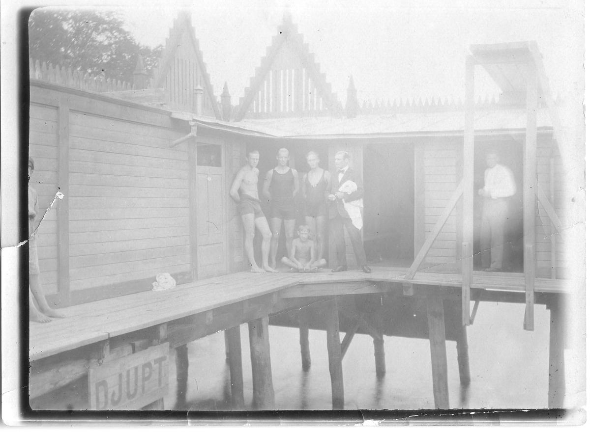 Kallbadhuset, nära Gamla kyrkogården. Badhuset byggdes 1904 och revs 1938. Arbogaån. Fem vuxna män och en pojke. Fyra personer i badkläder och två påklädda.