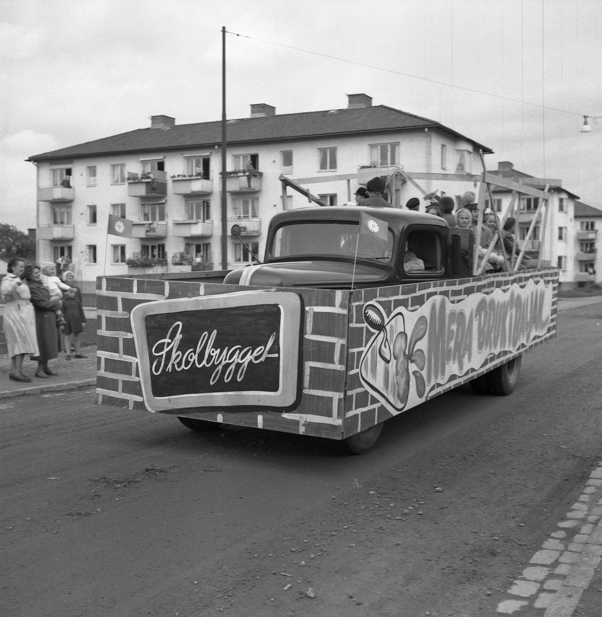 """Barnens Dag firas. En lastbid kör i paraden. """"Skolbygget"""" står det på en skylt i fronten. På flaket sitter flera barn. (Skolbygget kan syftas på Gäddgårdsskolan, som stod klar i augusti 1952)."""