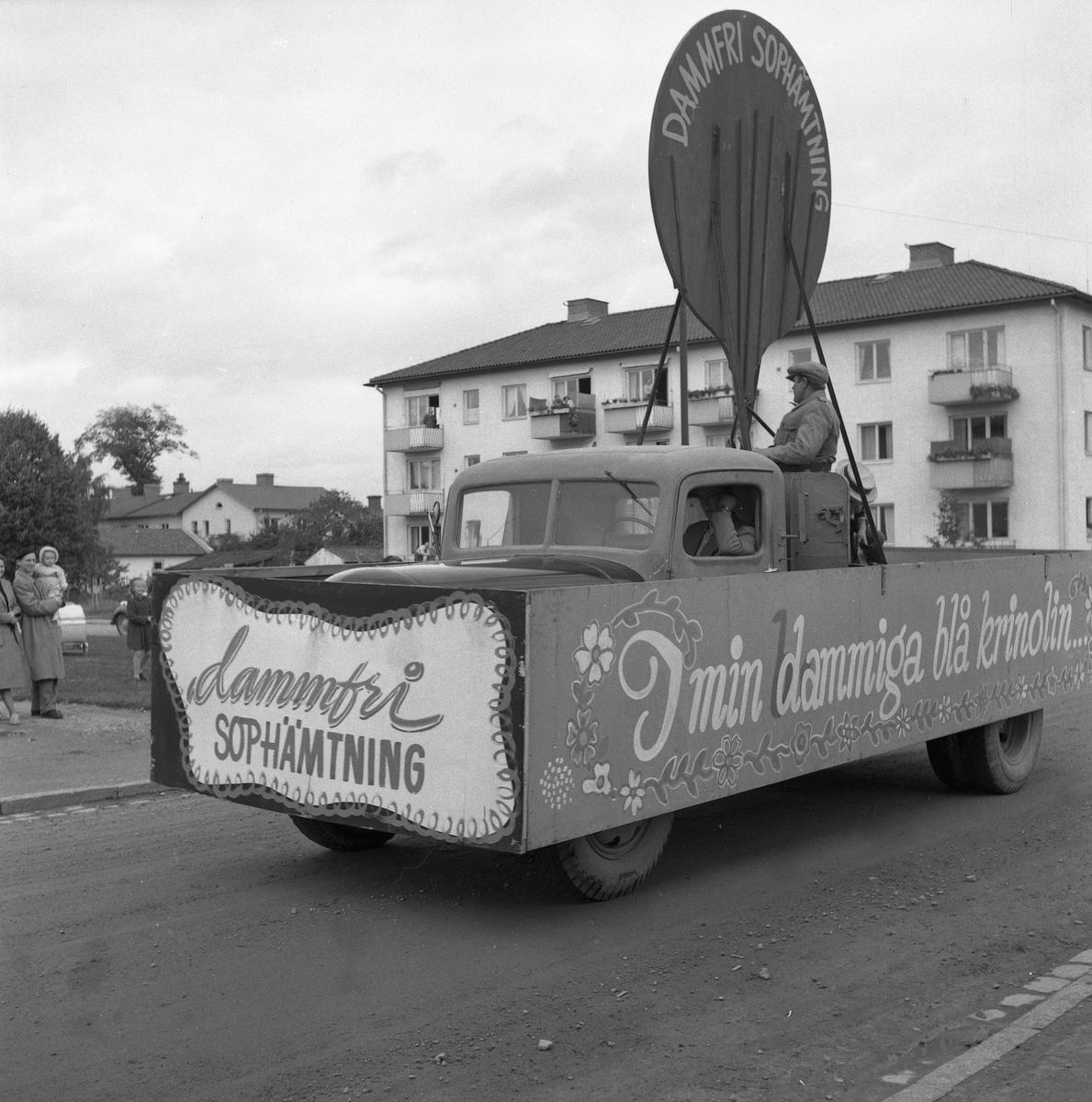 """Barnens Dag firas med en parad genom staden. En lastbil med texten """"dammfri sophämtning"""". En man är chaufför och en man står på flaket."""