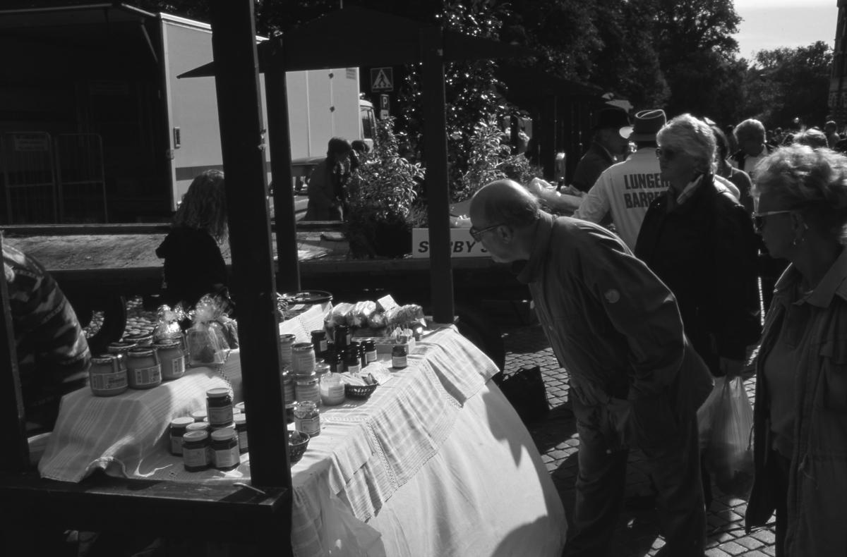 """Evenemanget """"Bonde på stan"""" pågår på Järntorget. Närmast i bild ses ett torgstånd med bland annat honung. Bo Jansson har hittat något intressant. Hustrun Barbro Jansson, ses längst till höger i bild. En man från Lunger ses bland försäljarna."""