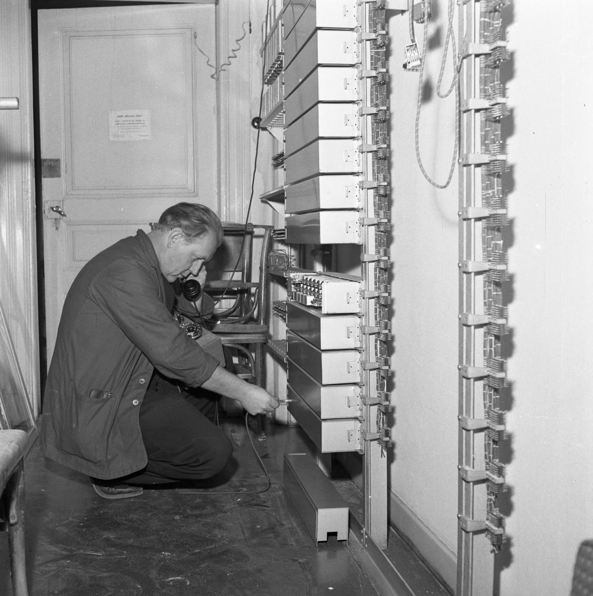 Efter branden på Televerket på Nygatan Lagningsarbete. En reparatör lyssnar i telefonluren.