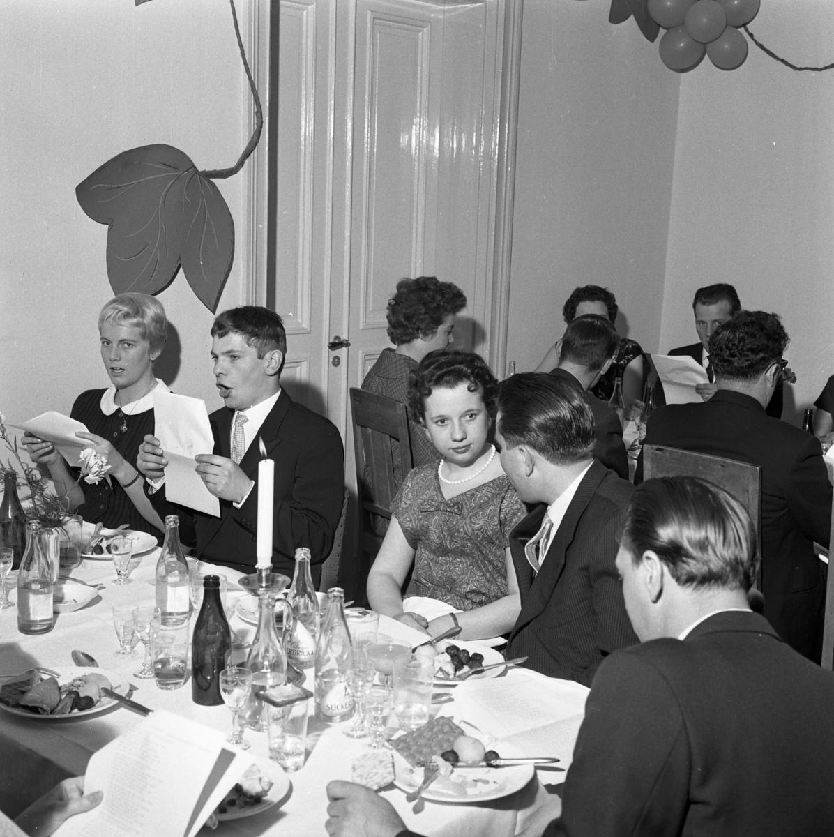 """Elektrikerförbundets Arbogaavdelning har jubileumsfest. Män och kvinnor vid dukade bord. Köttbullar och potatis på tallrikarna. """"Pyrra"""" Bergström med fru deltar i allsången. Fru Davidsson med make Lennart."""
