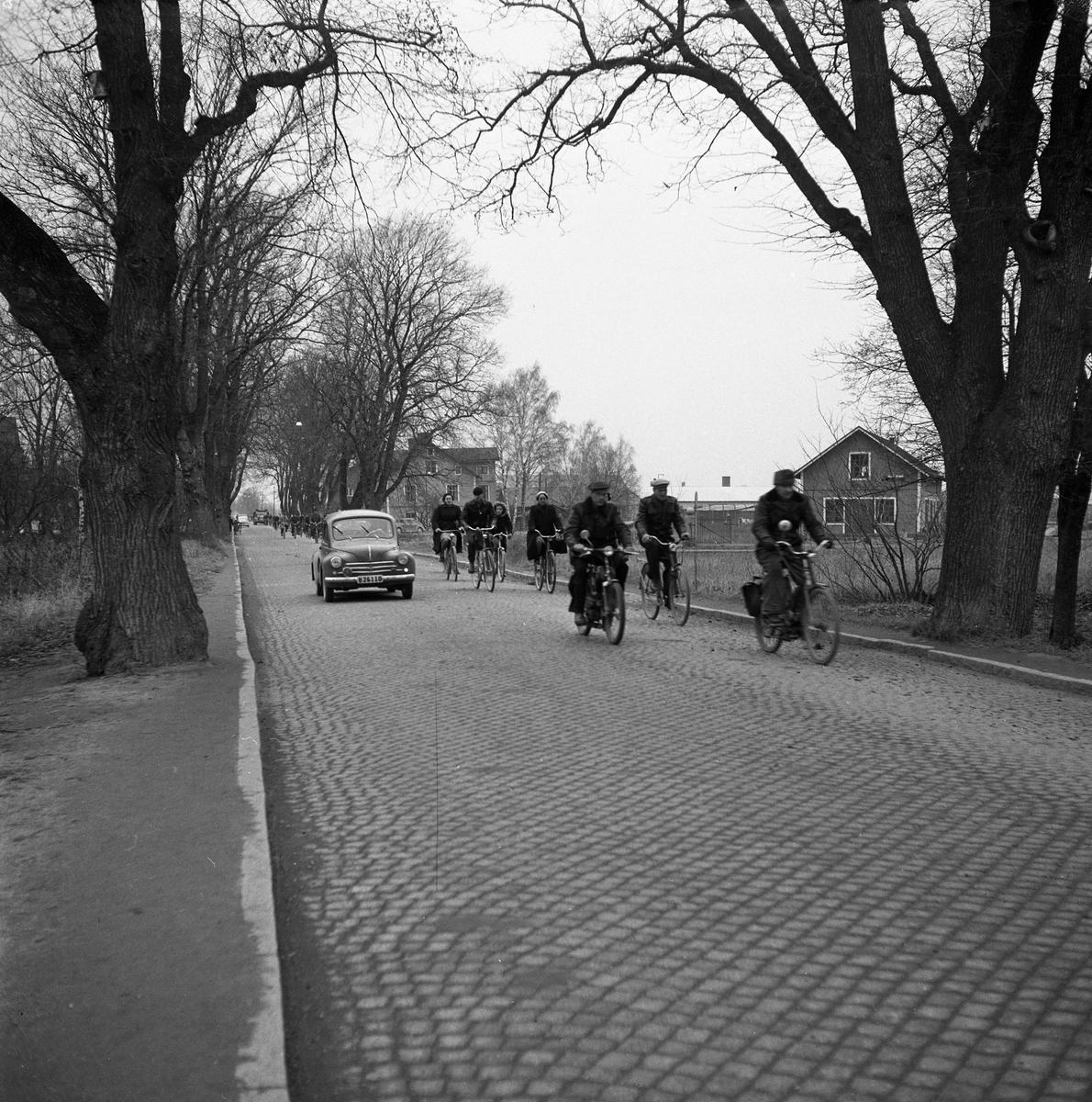 Jädersvägen. Män och kvinnor cyklar till arbetet på Arboga Mekaniska Verkstad. Huset, till vänster, är Gärstadal, bryggeribostäder. Bryggeriet ligger till höger, utanför bilden. En bil och en moped. Gatsten. AMV