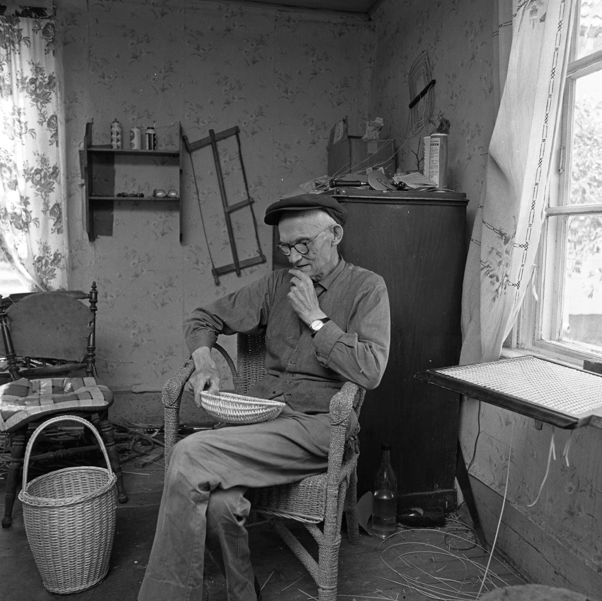 Korgmakare Oskar Larsson i Sjölunda, Tyringe. Oskar har sin verkstad i ett av rummen i bostadshuset. På väggen hänger en såg. På byrån ligger en borr. En färdig korg står på golvet. Vid fönstret ligger en snart färdig stolsits. Oskar är gift med Maja. Oskar lärde grannbarnen att spela schack.