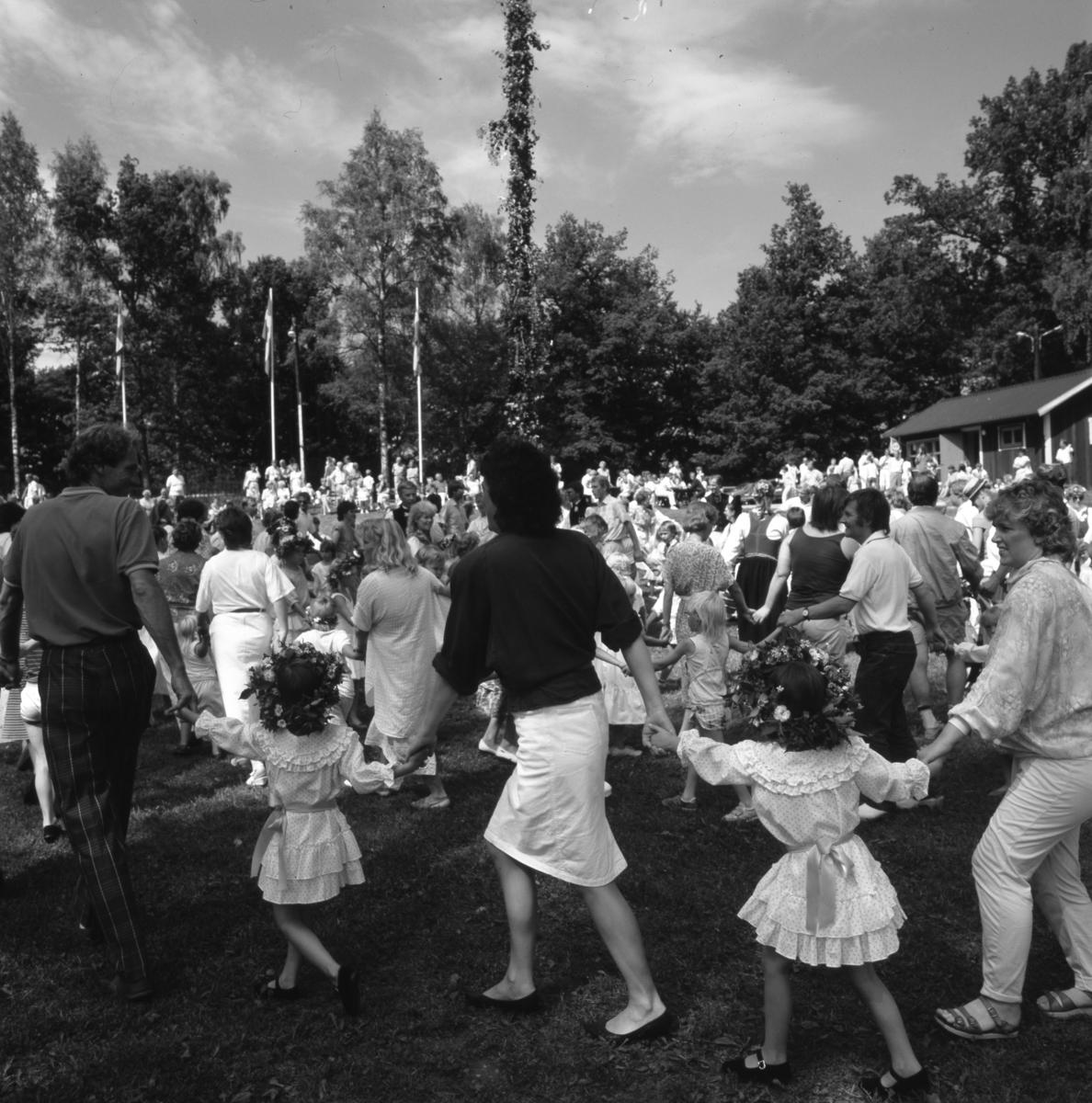 Det är midsommar och människor dansar ringdans runt midsommarstången. Några har blomsterkransar på huvudet. Midsommarstången är rest och flaggorna hissade. I huset finns en kiosk. Den som inte dansar kan sitta i gräset, eller på en medhavd campingstol, och titta på.
