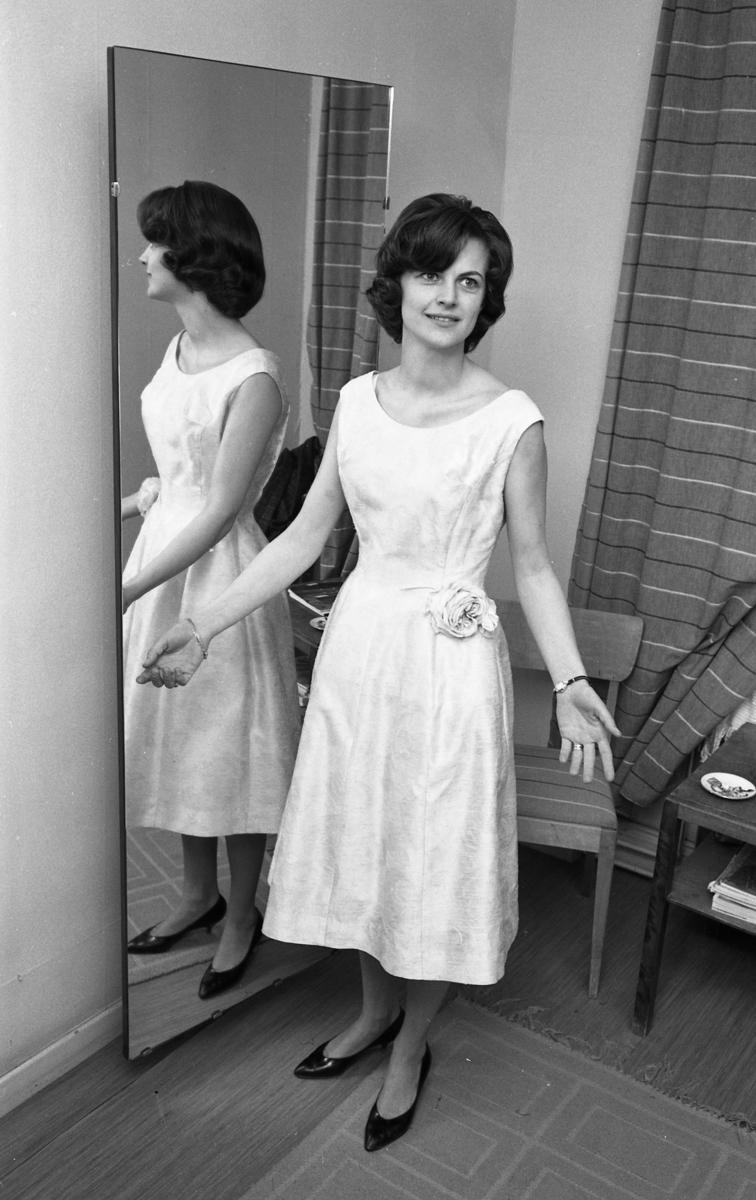 Marianne Rosenkvist är en av mannekängerna när Öhrman & Melander har sin modevisning på Folkan/Medborgarhuset. Här står hon i en klänning med prinsesskärning och blomdekoration i midjan.