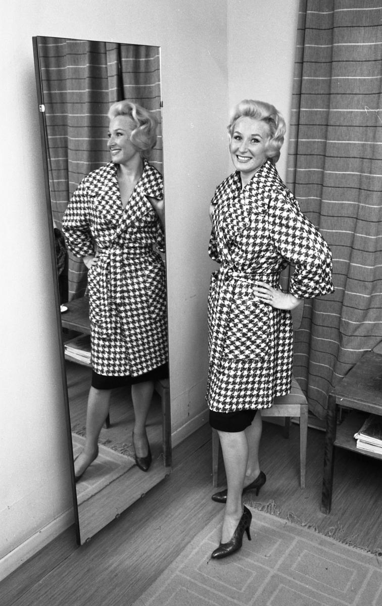 Kvinna i hundtandsmönstrad kappa. Hon står i ett omklädningsrum med spegel. Kvinnan är en av mannekängerna när Öhrman och Melander har sin modevisning på Folkan/Medborgarhuset.