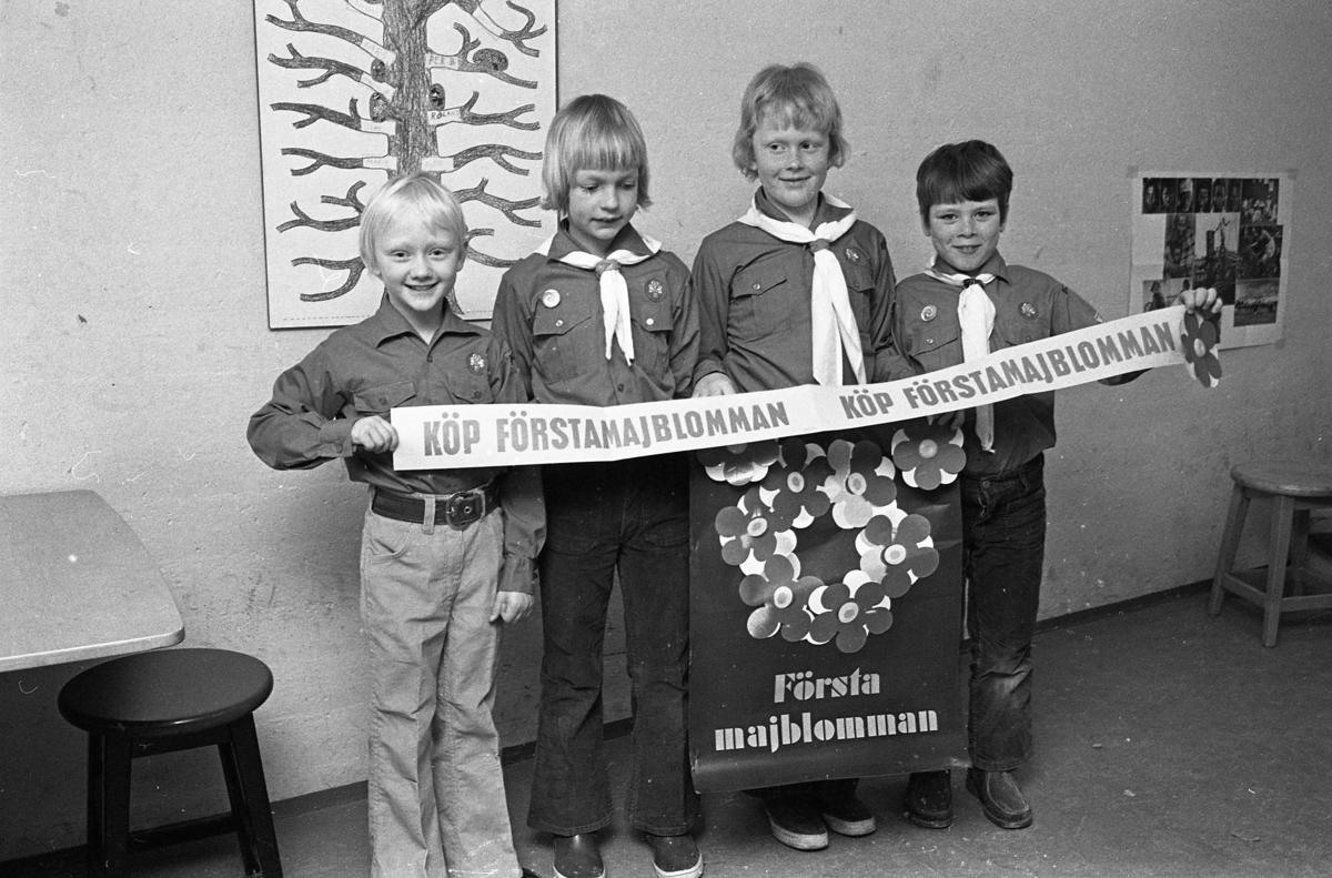 Scouter säljer majblommor. Fyra pojkar i scoutskjorta och sjal. De håller i en banderoll. Den tredje från vänster är Jens Gunnarsson.