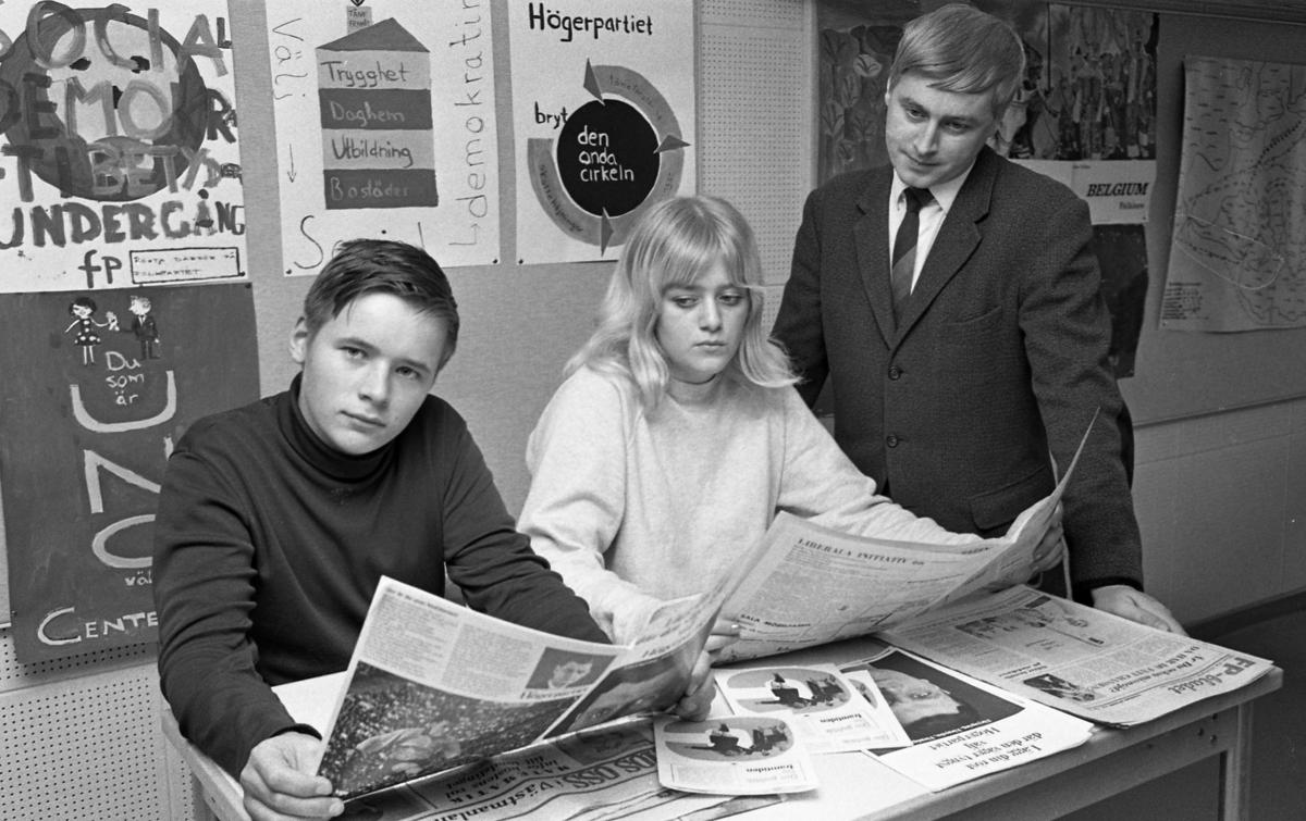 Årskurs 7 på Gäddgårdsskolan när sig om politik inför valet. Kari Simos och Gunilla Gustavsson läser var sin tidning. Lärare Kjell Dahlgren ser på.