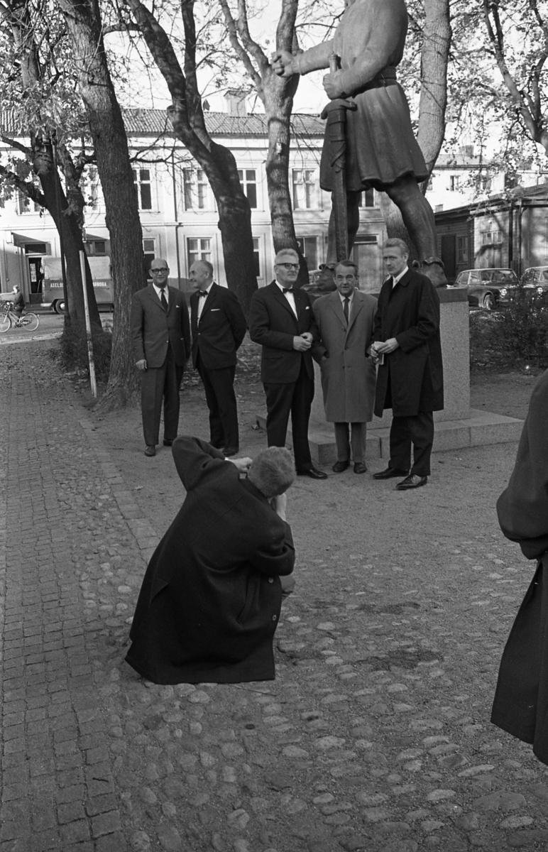 Statsutskottet besöker Arboga. Under Engelbrekts staty står Jonas Carlsson till vänster och Olle Göransson till höger. Mannen i mitten är okänd. En fotograf sitter på huk och tar en bild.
