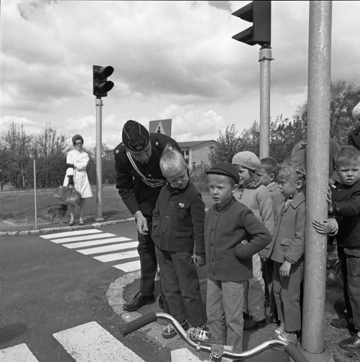 Trafiklekskola med polisman Leif Ekström, i uniform. Barnen får lära sig om trafikregler, trafikskyltar, övergångsställen och trafikljus. Några mammor är också med. I bakgrunden står en kvinna med en hund. Gäddgårdsskolan skymtar till höger. Platsen är i anslutning till Borgmästargatan.