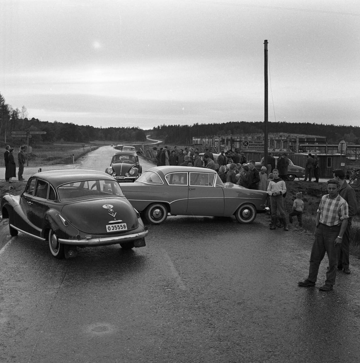 """Två bilar har krockat på vägen mot Örebro. På vägskyltarna, till vänster, står det """"Katrineholm"""", """"Västermo kyrka"""" och """"Stadens centrum"""". Till höger håller Koppartrans på att bygga en bensinstation. Män, kvinnor och barn har samlats för att se på krocken. Ett par bilar kan inte ta sig fram eftersom färdriktningen är blockerad."""