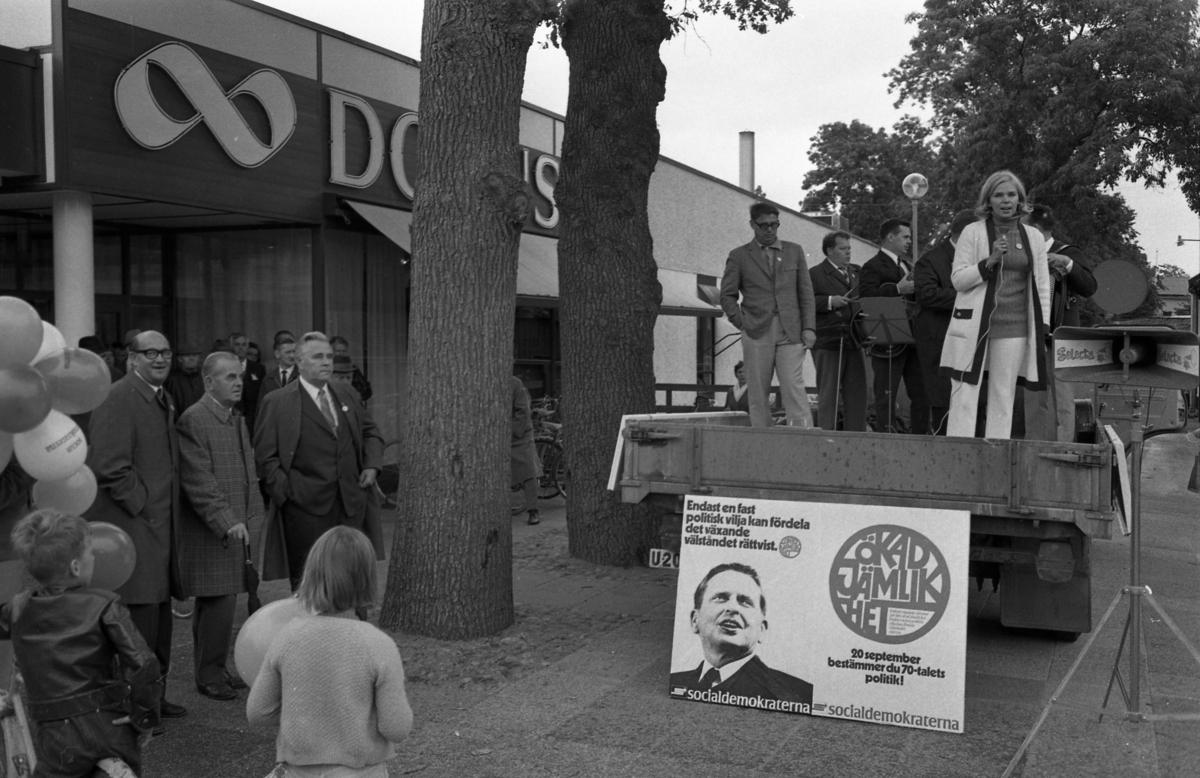 Socialdemokraterna har valmöte utanför Domus. Till vänster, under almarna, står tre herrar; i mitten Gustav Danielsson och till höger Nils Brodin. Från ett lastbilsflak valtalar Berit Oscarsson. Bakom henne står orkestern Select. Nedanför Berit står en stor valaffisch med Olof Palme på.