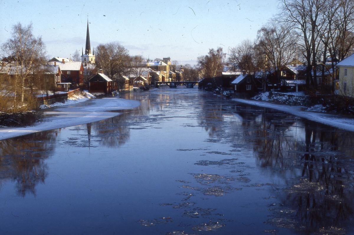 Vintervy över ågårdar på Västerlånggatan och Storgatan. Is på Arbogaån. Snö på hustaken. Kapellbron. Till vänster ses Heliga Trefaldighetskyrkan. I bakgrunden, mitt i bilden, ses Centralföreningens silo/Lantmännens silo och Brandstationen på Strandvägen. Bilden är tagen från Strömsnäsbron